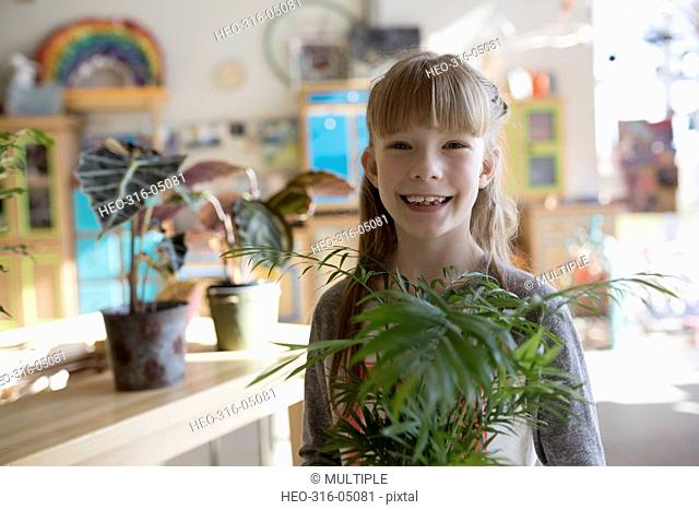 Portrait smiling girl holding plant in science center