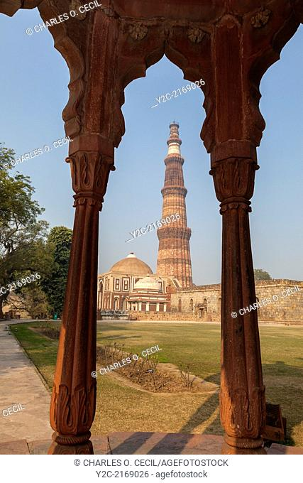 New Delhi, India. Qutb Minar, a Victory Tower and minaret, 13th. Century, in background, seen through two pillars of Smith's Folly