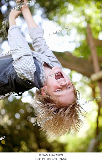 Playful boy hanging upside-down from rope swing