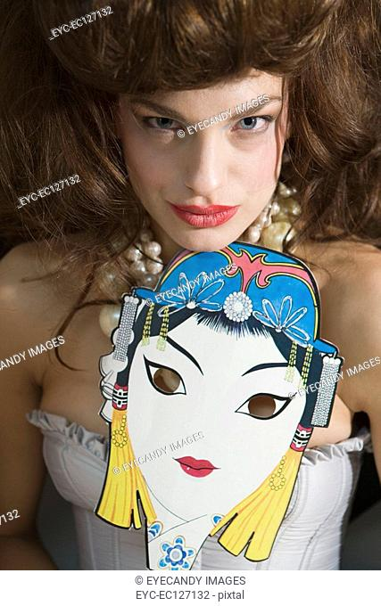 Portrait of woman in corset holding Asian masquerade mask