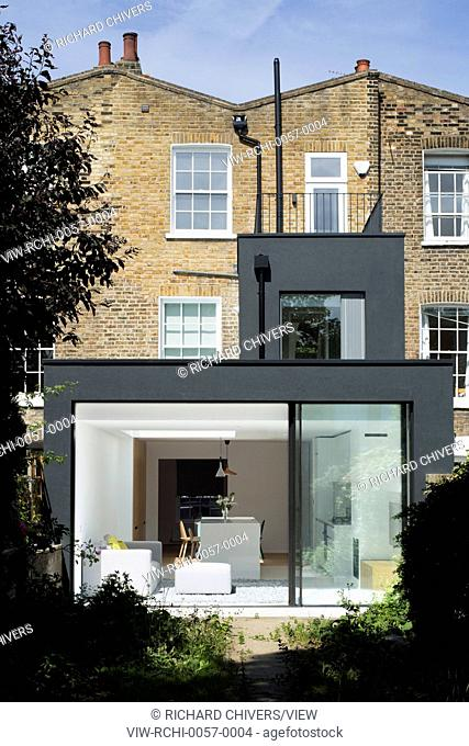 The rear extension is realised as two stacked black boxes, providing a strong visual contrast against the rich mix of London Sto