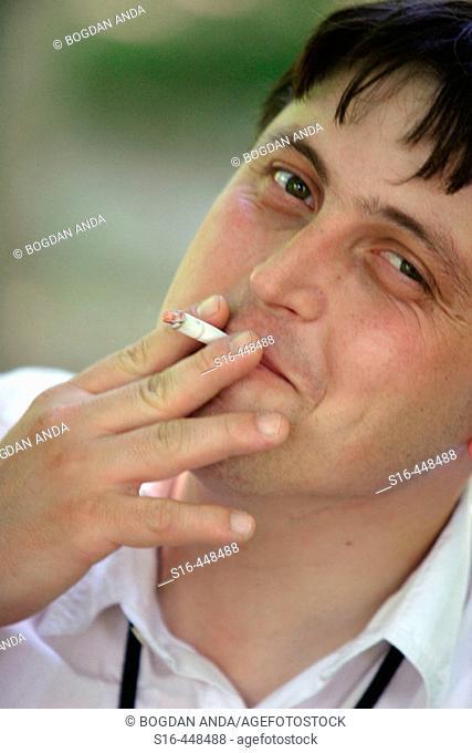 Amused man smoking with passion