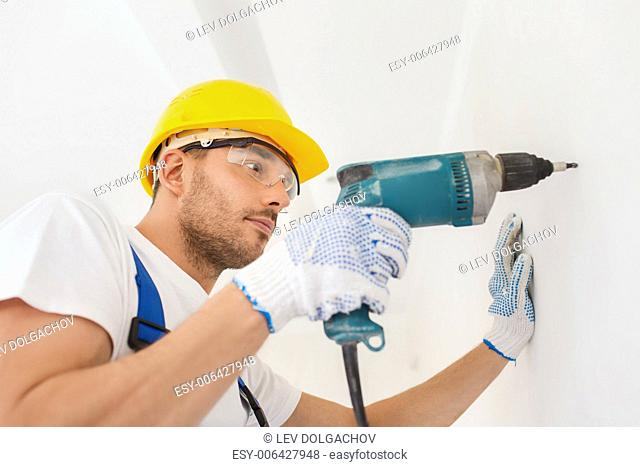 building, working equipment and people concept - builder in hardhat perforating wall with drill indoors