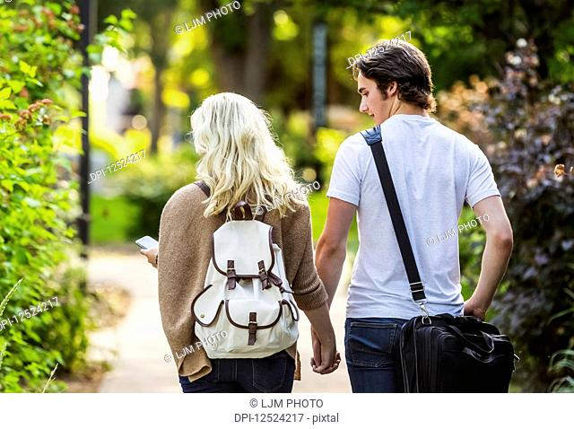 A young couple walking down a path on the university campus holding hands and the woman is checking her smart phone for messages; Edmonton, Alberta, Canada