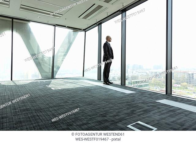 Businessman on empty office floor looking out of window