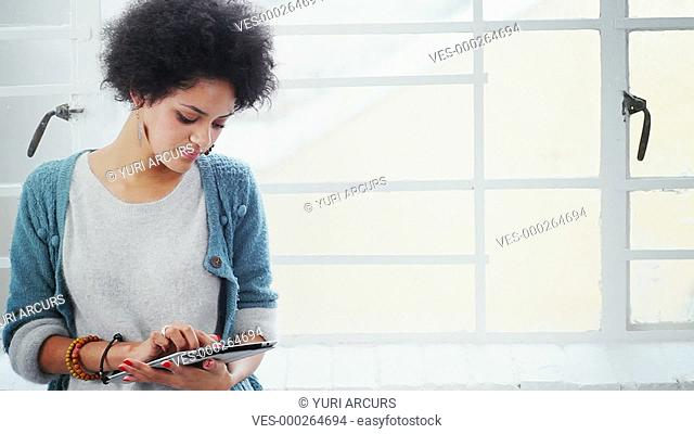 Pretty multi-ethnic woman using a touchpad looking up and smiling at you