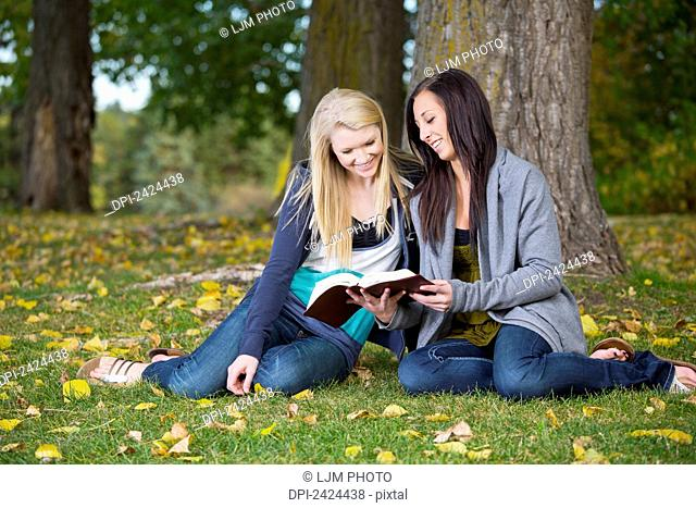 Two teenage girls reading the Bible together in a park; Edmonton, Alberta, Canada
