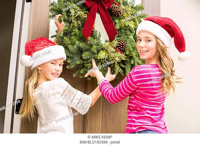 Caucasian girls hanging Christmas wreath