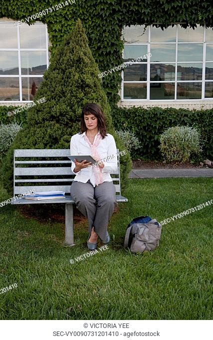 Businesswoman working on bench