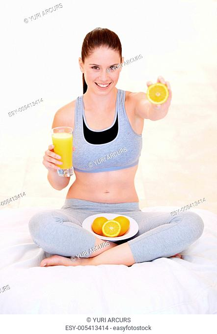 Playful young woman with a glass of orange juice and fresh oranges