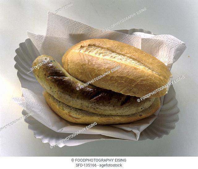 A sausage (Bratwurst) in a roll on paper plate