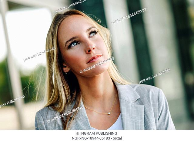 Blond girl wearing casual clothes in the street. Female with blue eyes. Beautiful young caucasian woman in urban background