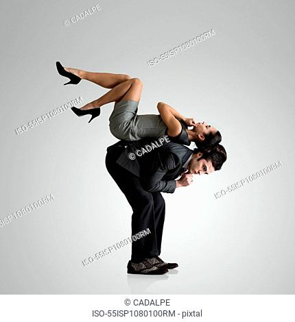 Woman lying on top of man's back