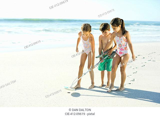 Children using metal detector on beach