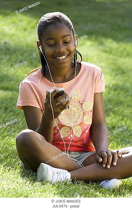 Girl 11-13 sitting on grass in park, listening to MP3 player, smiling, front view tilt