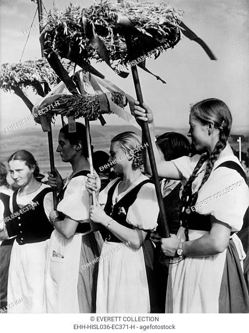 German women wearing traditional folk costumes during the 1935 Erntedankfest. 'Peasant women' hold beribboned wreaths with during the Nazi celebration