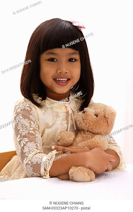 young girl holding teddy bear and smiling