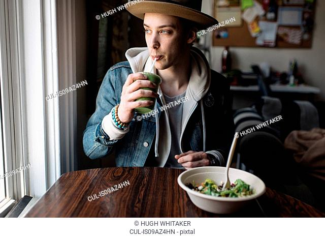 Young man sitting at table, having meal, drinking health drink