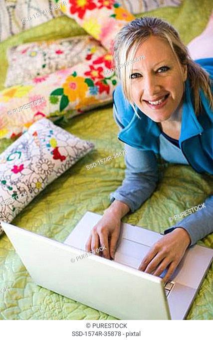 Woman working on laptop in bedroom
