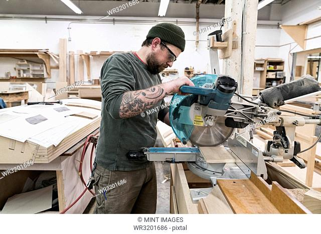 Caucasian male carpenter using a radial saw to cut a piece of wood in a large woodworking factory