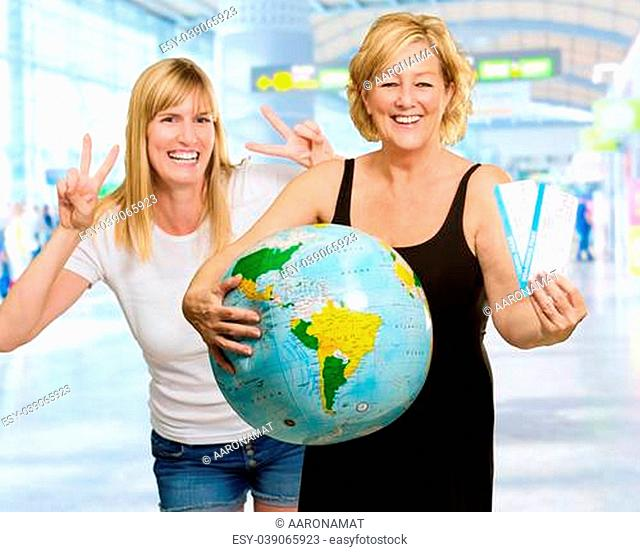 Mature Woman Holding Globe In Front Of Happy Young Woman, Indoor