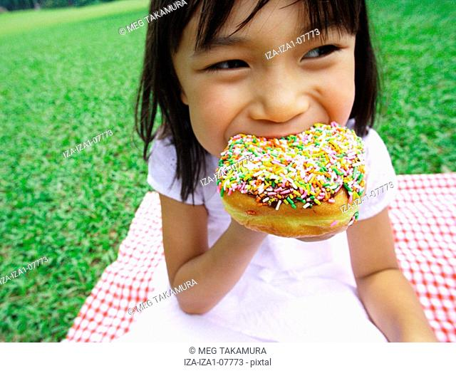 Close-up of a girl eating a donut in a park