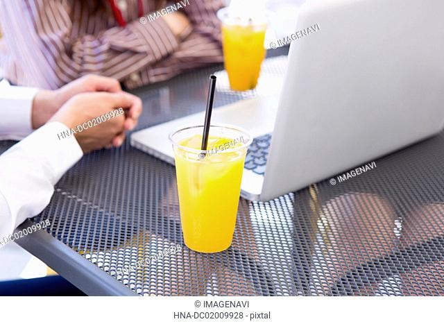 A laptop and a glass of juice at outdoor seat