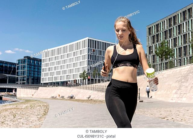 Young woman running and using smartphone in city, Berlin, Germany