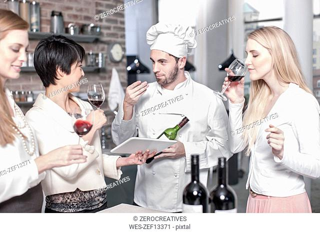 Chef with three women tasting red wine in kitchen
