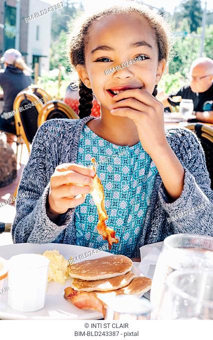 Smiling Mixed Race girl eating breakfast at restaurant