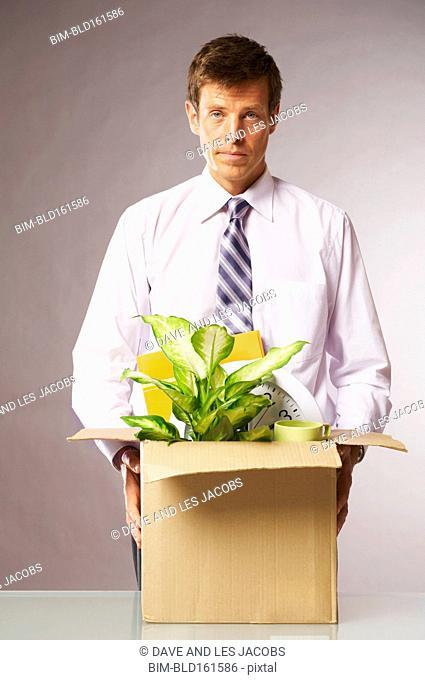 Caucasian businessman with cardboard box leaving job