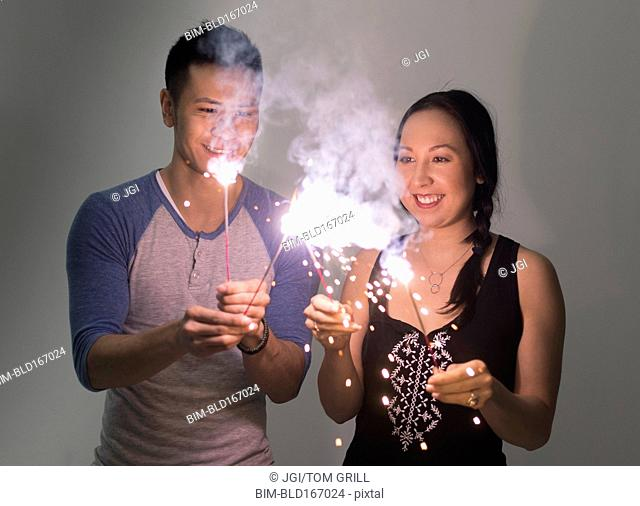 Smiling couple playing with sparklers