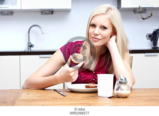 Blond young woman holding pastry