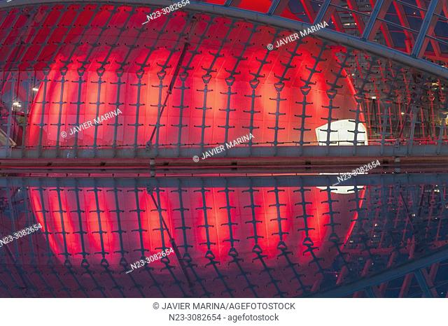 Hemisferic building illuminated in the city of arts and sciences, behind the building Torre de Francia, Valencia, Spain