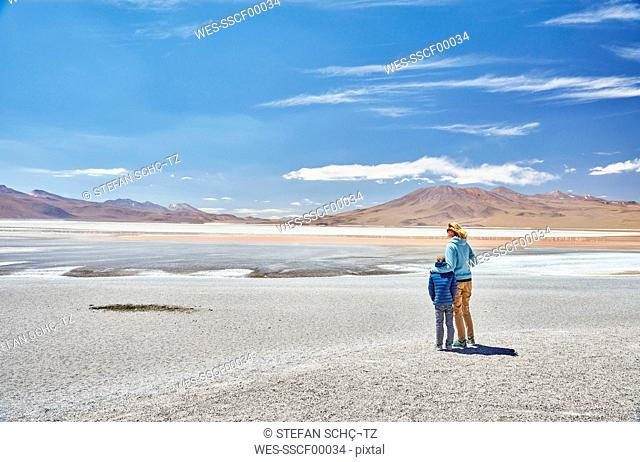 Bolivia, Laguna Colorada, mother and son at lakeshore with view to the Andes