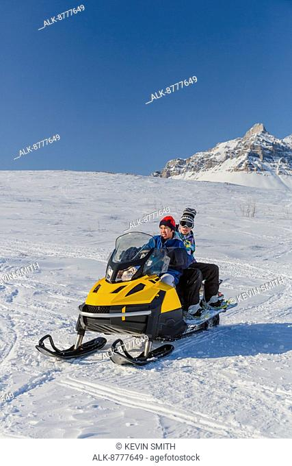 Snowboarders riding on a snowmachine, Anaktuvuk Pass, Winter, Gates of the Arctic National Park, Brooks Range, Arctic Alaska