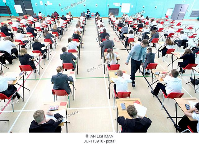 Middle school students taking examination at desks in school gymnasium