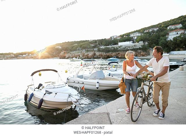 Senior couple with bicycle walking on quay at evening twilight