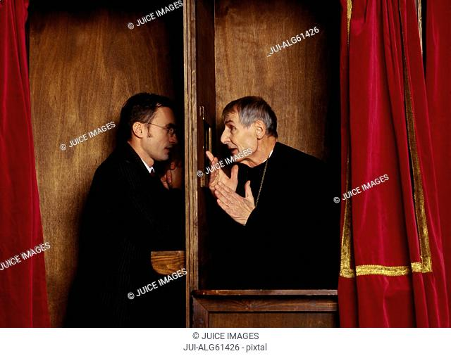 Businessman in confessional with priest