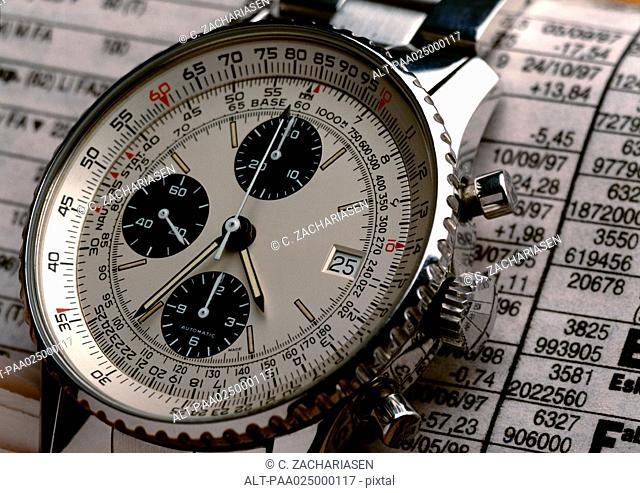 Wristwatch on top of stock report, extreme close-up