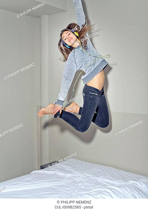 Woman in mid air jumping on bed