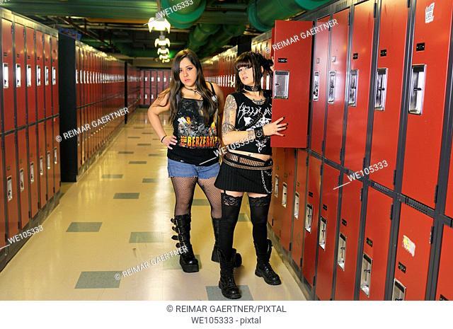 Two young female heavy metal punk rockers in a basement school locker room