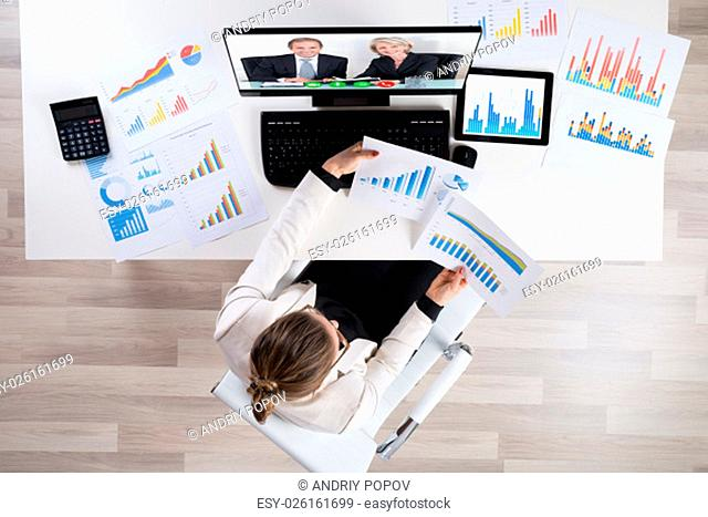 High Angle View Of Businesswoman With Graphs Videoconferencing On Computer