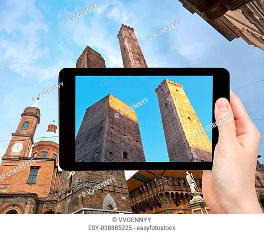 travel concept - tourist takes picture of Due Torri -two tower - symbol of city in Bologna, Italy on tablet pc