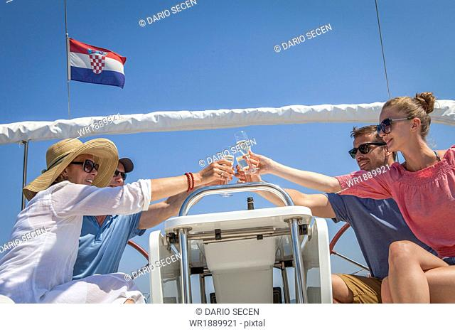 Two couples on sailboat, drinking champagne, Adriatic Sea, Croatia