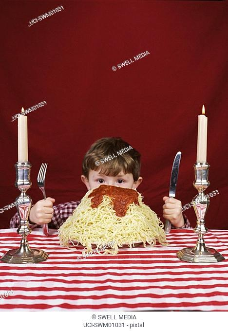 Young boy hiding behind giant plate of spaghetti