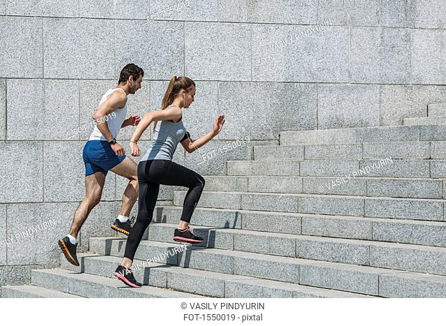 Determined friends jogging up steps by wall