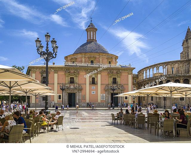People sitting in outdoor cafes in the Plaza de la Virgen opposite the Basilica Virgin de los Desamparados (centre) and the Cathedral, Cuitat Vella, Valencia