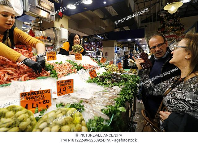 22 December 2018, Spain, Palma de Mallorca: Carmen (M) offers her customers Victoria and Francisco mussels while Marta places the shrimps in the display of her...
