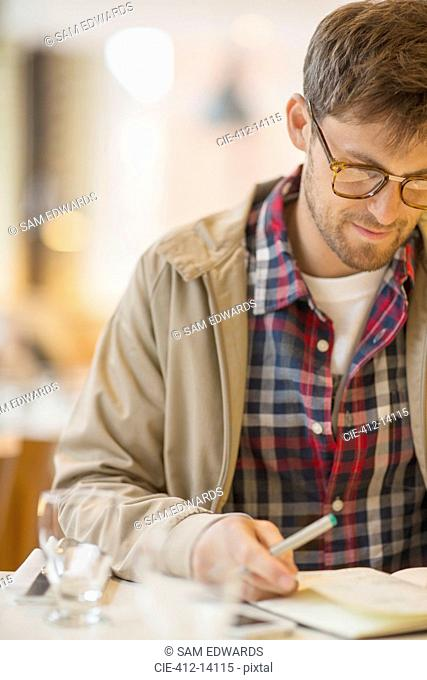 Man writing in cafe